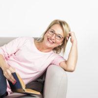 donna-matura-sorridente-che-si-appoggia-il-libro-della-tenuta-del-sofa-a-disposizione-contro-il-contesto-bianco_23-2148043515