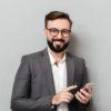 l-uomo-sorridente-nel-messaggio-di-testo-digitante-della-camicia-bianca-o-lo-scorrimento-inserisce-la-rete-sociale-facendo-uso-dello-smartphone-sopra-grey_171337-634
